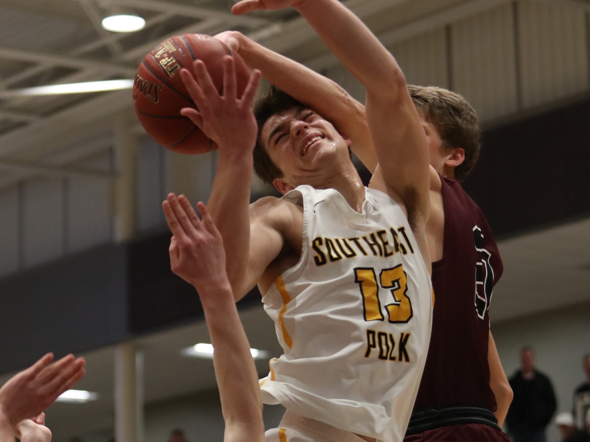 Southeast Polk's Dominic Caggiano (13) is fouled by Dowling Catholic's Ryan Riggs (21) during their game at Johnston High School in Johnston, Iowa, on Tuesday, Feb. 26, 2019. Dowling won the game 44-40 to advance to state.
