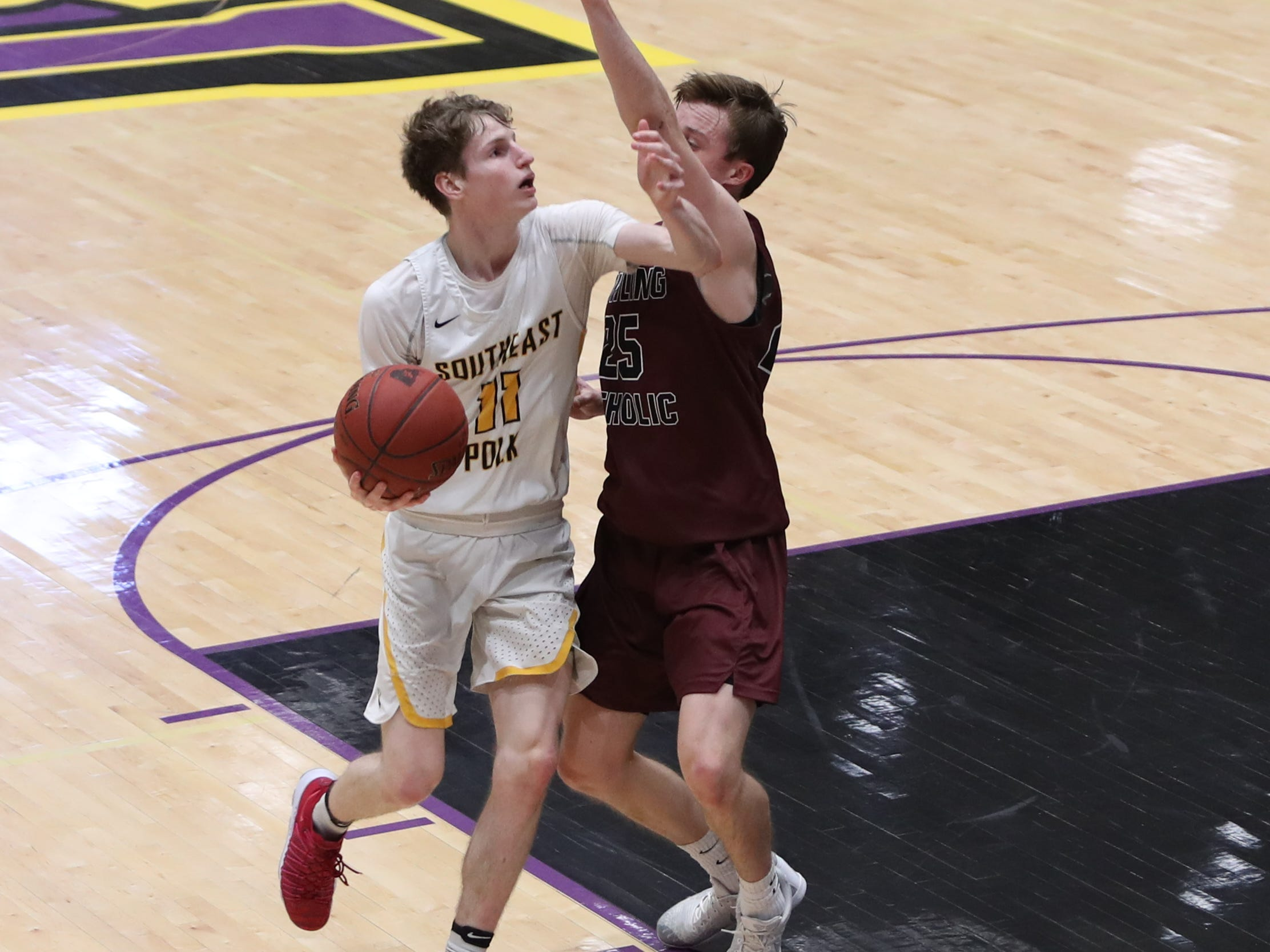 Dowling Catholic's Matt Stilwill (25) defends Southeast Polk's Sam Glenn (11) during their game at Johnston High School in Johnston, Iowa, on Tuesday, Feb. 26, 2019. Dowling won the game 44-40 to advance to state.