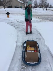 Girl Scout of Great Iowa member Eva Jones, age 10, pulls a sled laden with cookies down a snowy sidewalk in central Iowa.