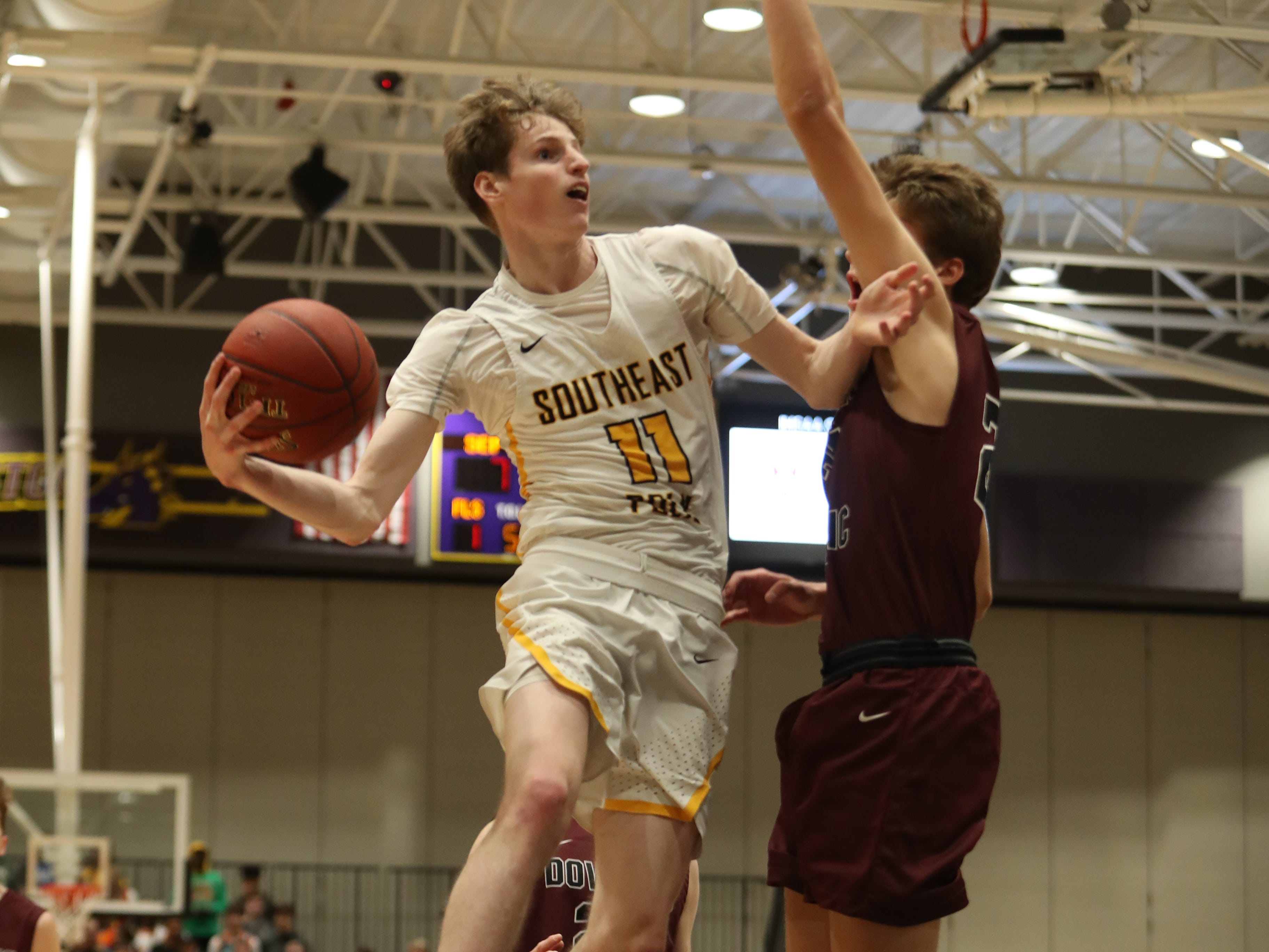 Dowling Catholic's Ryan Riggs (21) defends the shot of Southeast Polk's Sam Glenn (11)  during their game at Johnston High School in Johnston, Iowa, on Tuesday, Feb. 26, 2019. Dowling won the game 44-40 to advance to state.