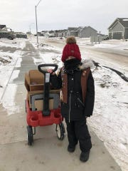 Girl Scout of Great Iowa member Audrey Baxter, age 6, pulls a wagon down a snowy sidewalk as she braves the cold to try and sell cookies in central Iowa.