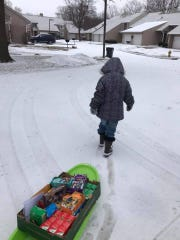 Girl Scout Aubrey Hogue, 7, pulls a collection of cookies on a sled through the snow and cold that has hit much of central and western Iowa throughout the month of February.