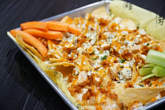 Buffalo chicken nachos made with fried chicken, smoked cheddar cheese sauce, buffalo sauce, carrot, celery, blue cheese crumbles and ranch from Court 7 Munchery at Smash Park.