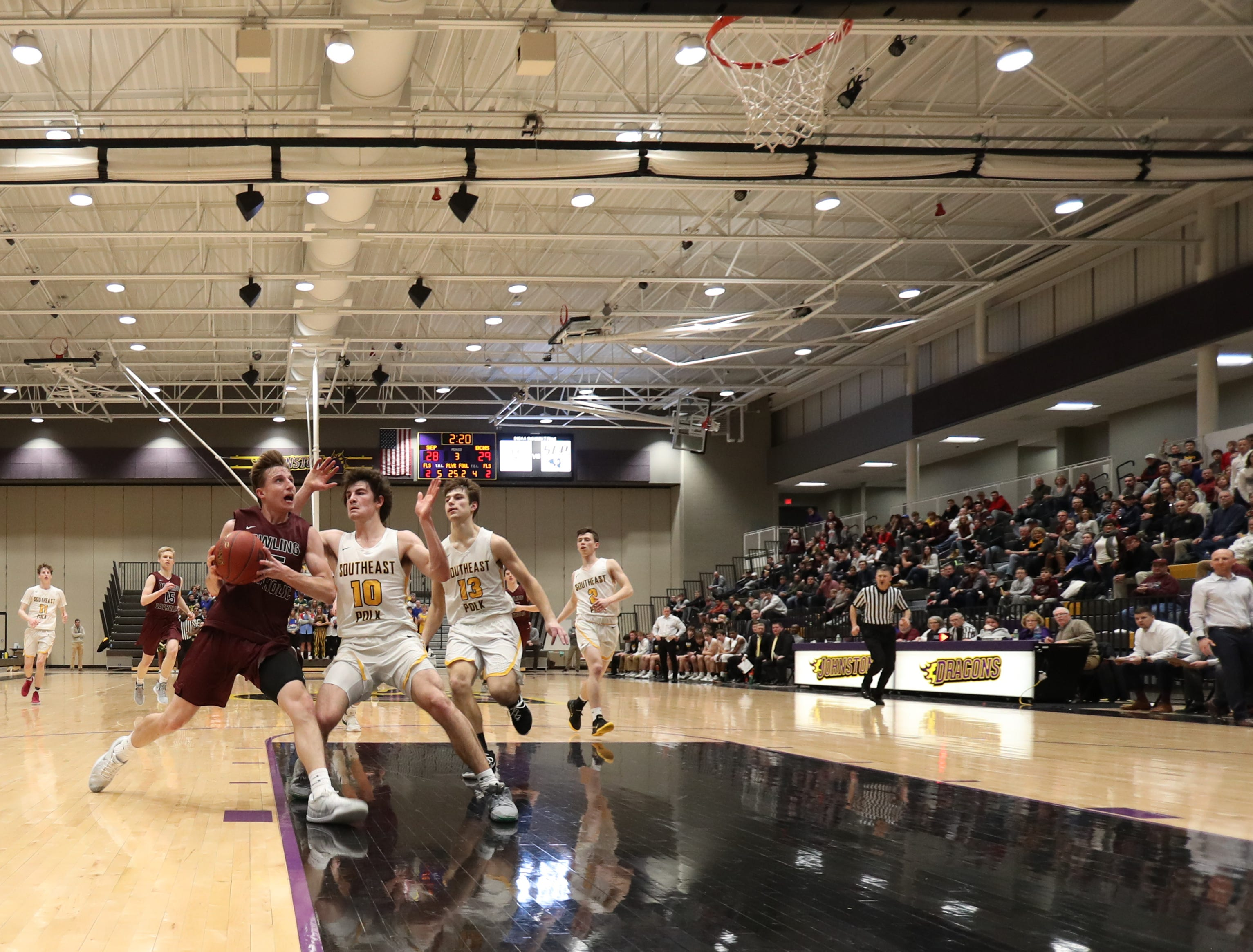 Dowling Catholic's Matt Stilwill (25) drives past Southeast Polk's Rams Daniel Hackbarth (10) during their game at Johnston High School in Johnston, Iowa, on Tuesday, Feb. 26, 2019. Dowling won the game 44-40 to advance to state.