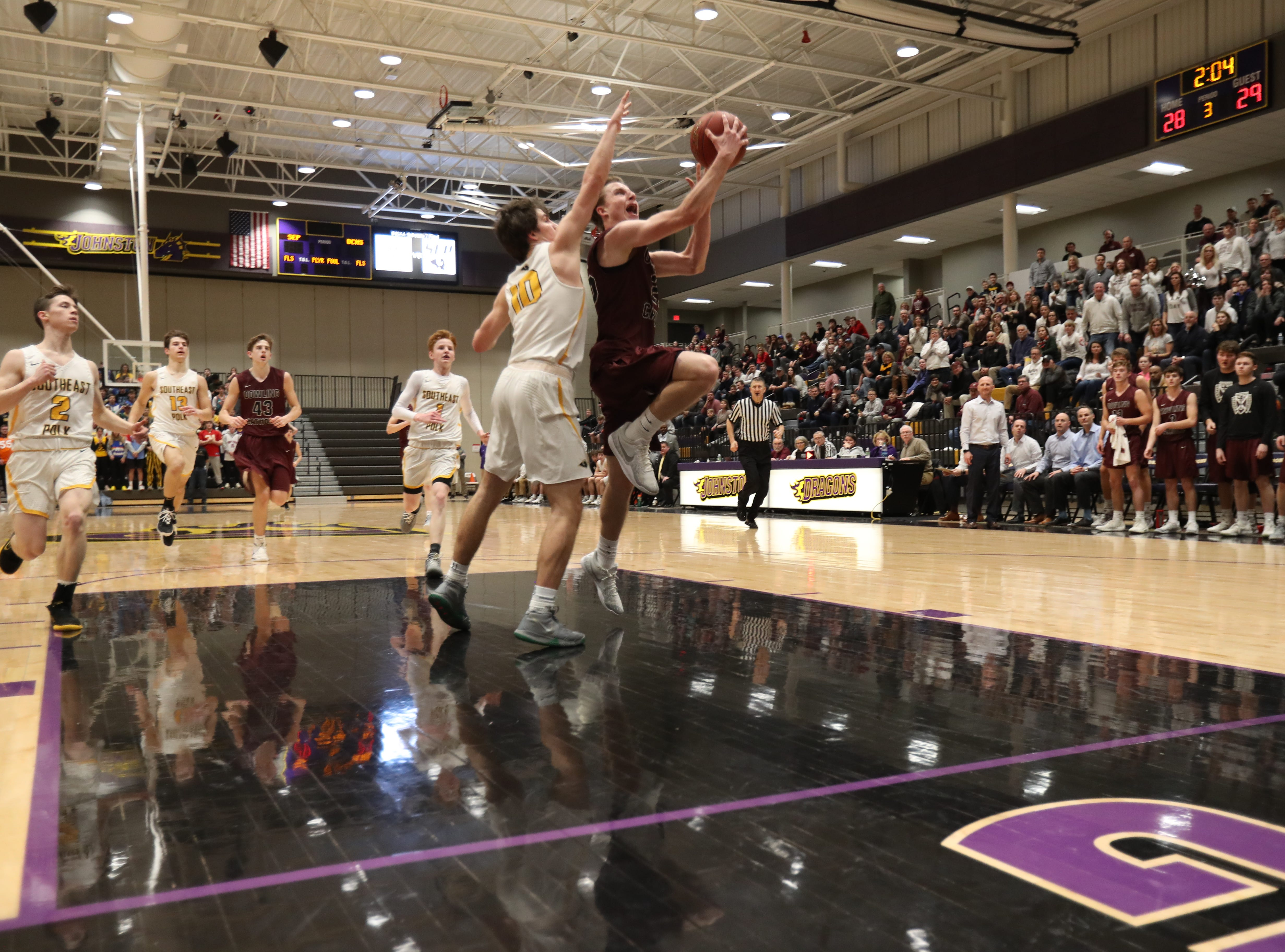 Dowling Catholic's Matt Stilwill (25) drives past Southeast Polk's Daniel Hackbarth (10) during their game at Johnston High School in Johnston, Iowa, on Tuesday, Feb. 26, 2019. Dowling won the game 44-40 to advance to state.