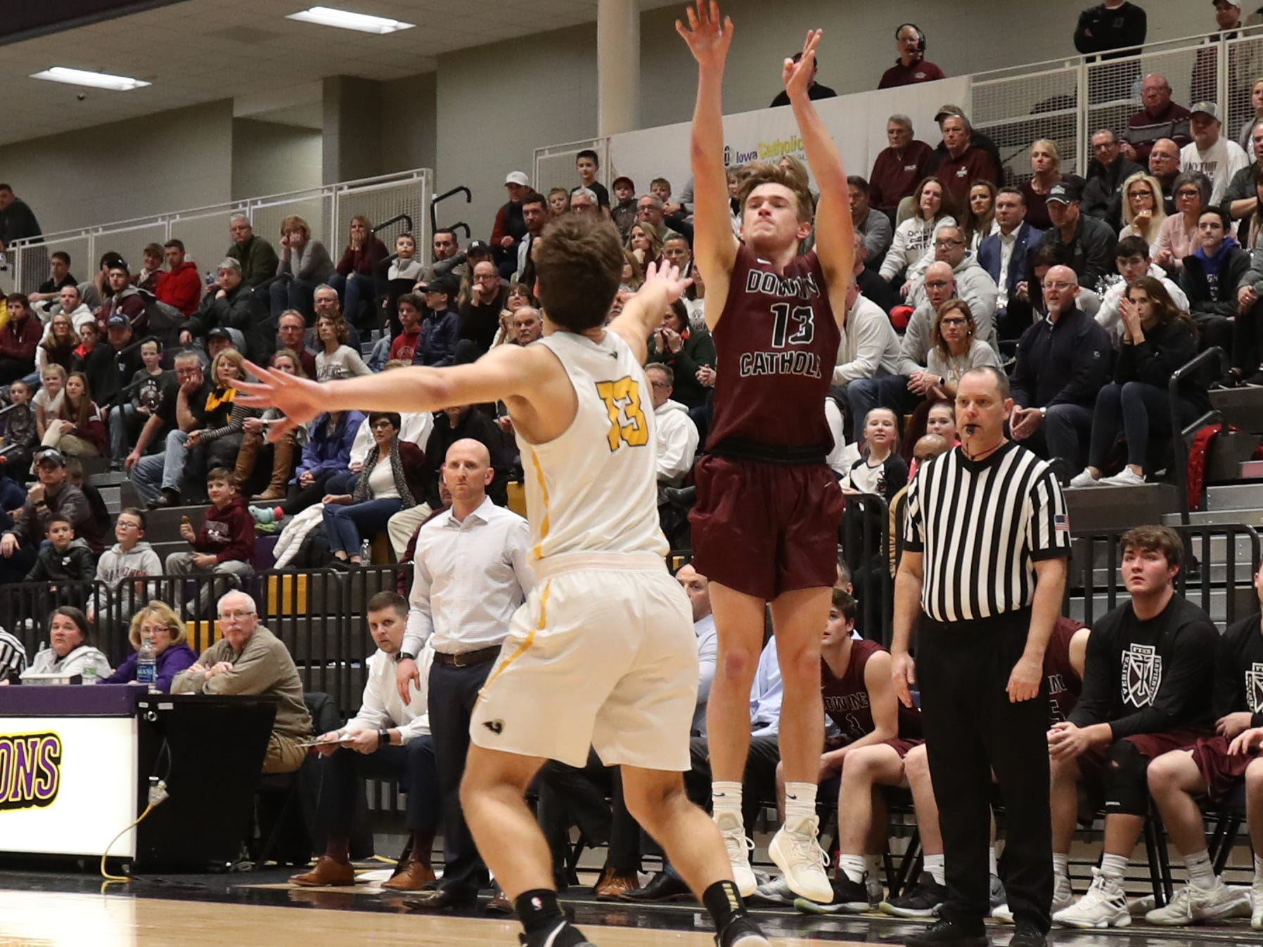Dowling Catholic's Jack Lyman (13) shoots over the hand of Southeast Polk's Dominic Caggiano (13) during their game at Johnston High School in Johnston, Iowa, on Tuesday, Feb. 26, 2019. Dowling won the game 44-40 to advance to state.
