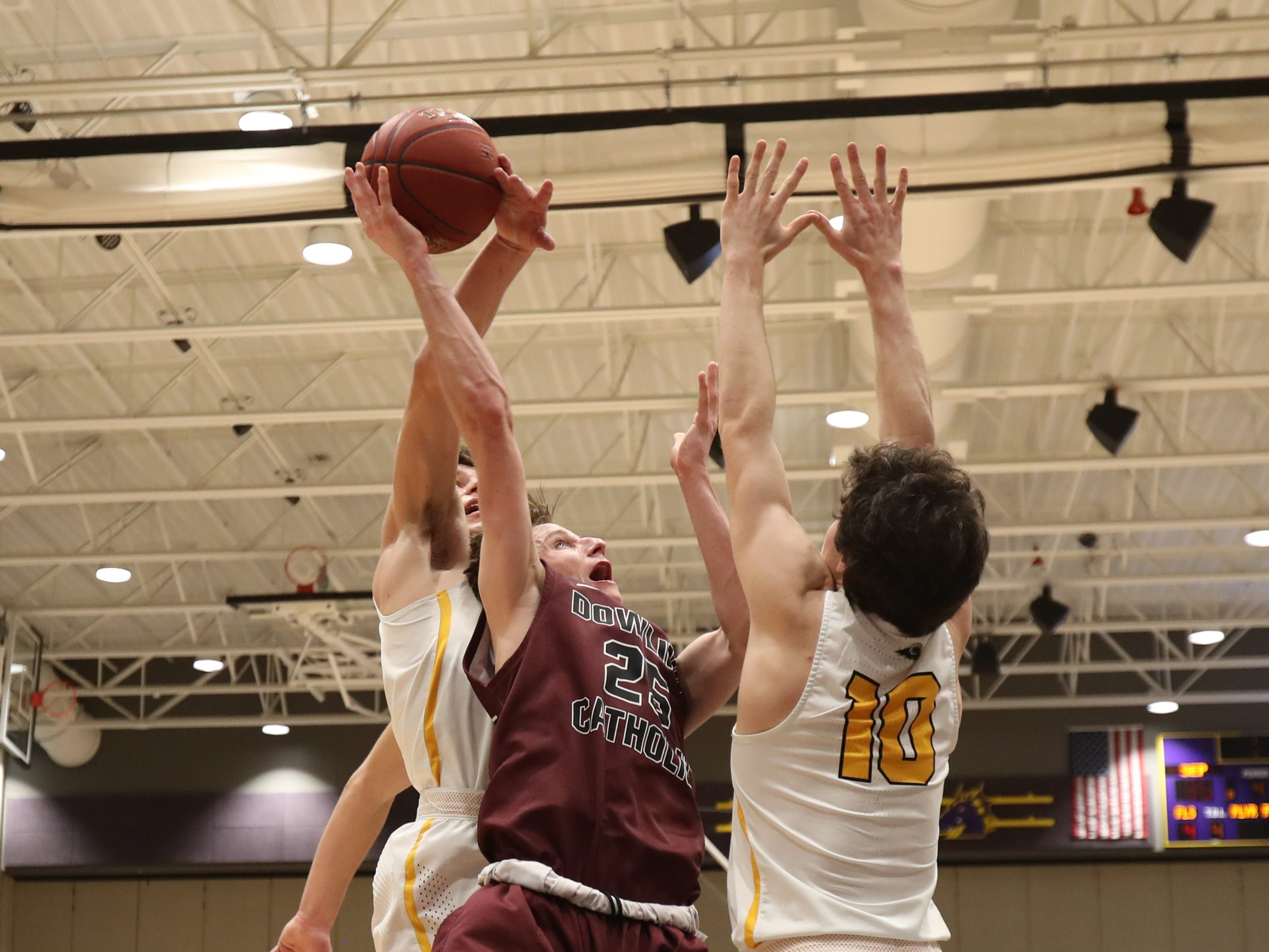 Southeast Polk's Dominic Caggiano (13) blocks the shot of Dowling Catholic's Matt Stilwill (25) during their game at Johnston High School in Johnston, Iowa, on Tuesday, Feb. 26, 2019. Dowling won the game 44-40 to advance to state.