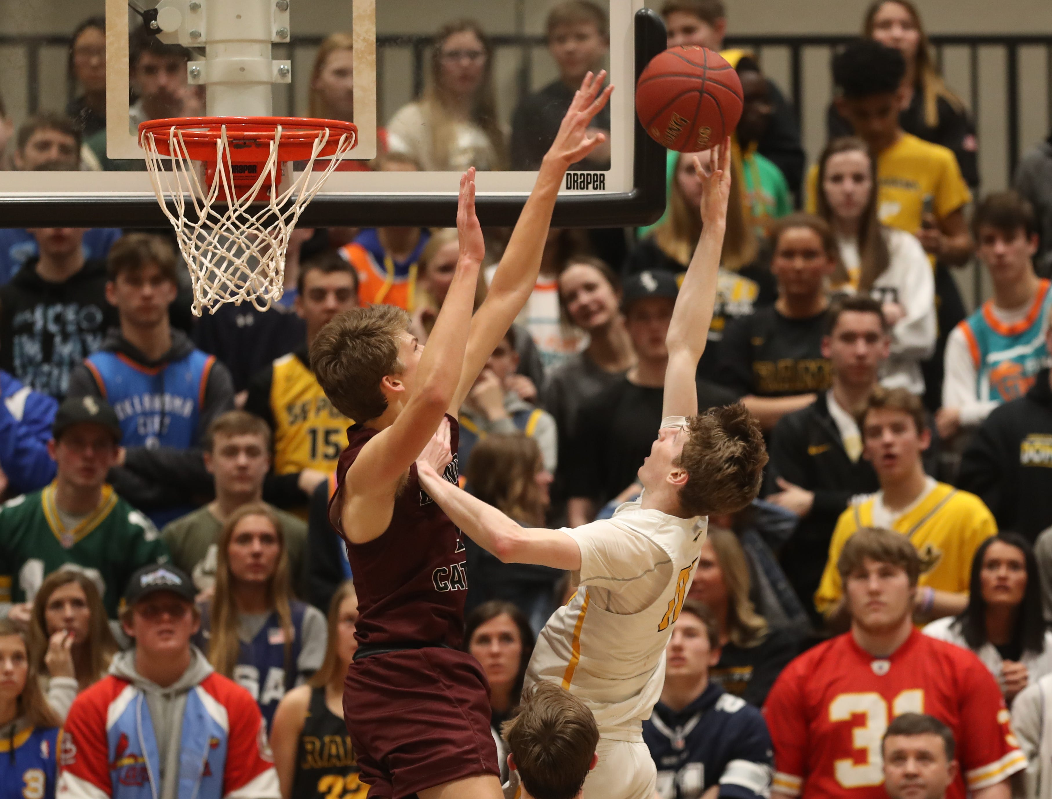 Dowling Catholic's Ryan Riggs (21) blocks the shot of Southeast Polk's Sam Glenn (11) during their game at Johnston High School in Johnston, Iowa, on Tuesday, Feb. 26, 2019. Dowling won the game 44-40 to advance to state.
