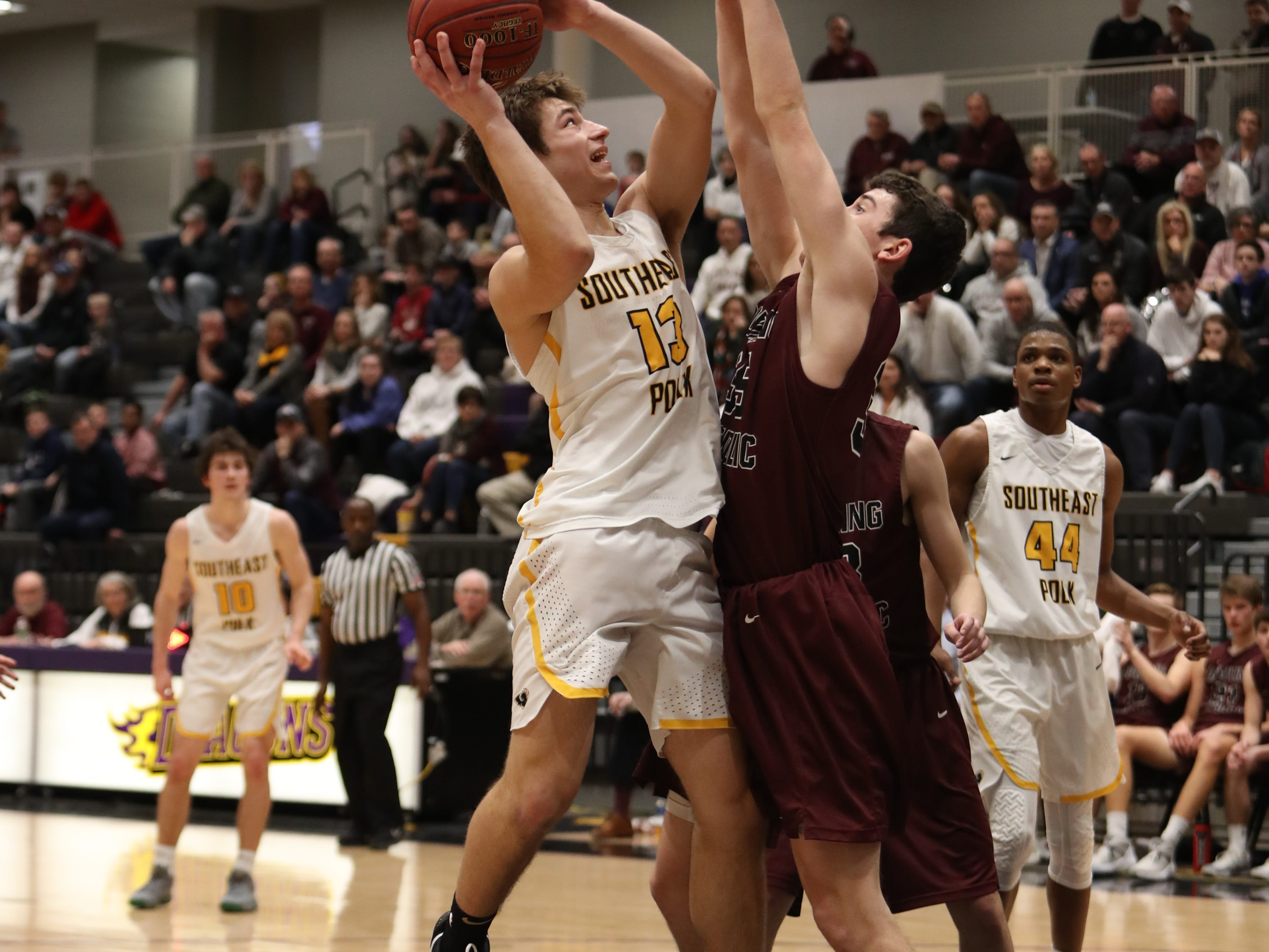Dowling Catholic's Andrew Lentsch (35) defends the shot of Southeast Polk's  Dominic Caggiano (13) during their game at Johnston High School in Johnston, Iowa, on Tuesday, Feb. 26, 2019. Dowling won the game 44-40 to advance to state.