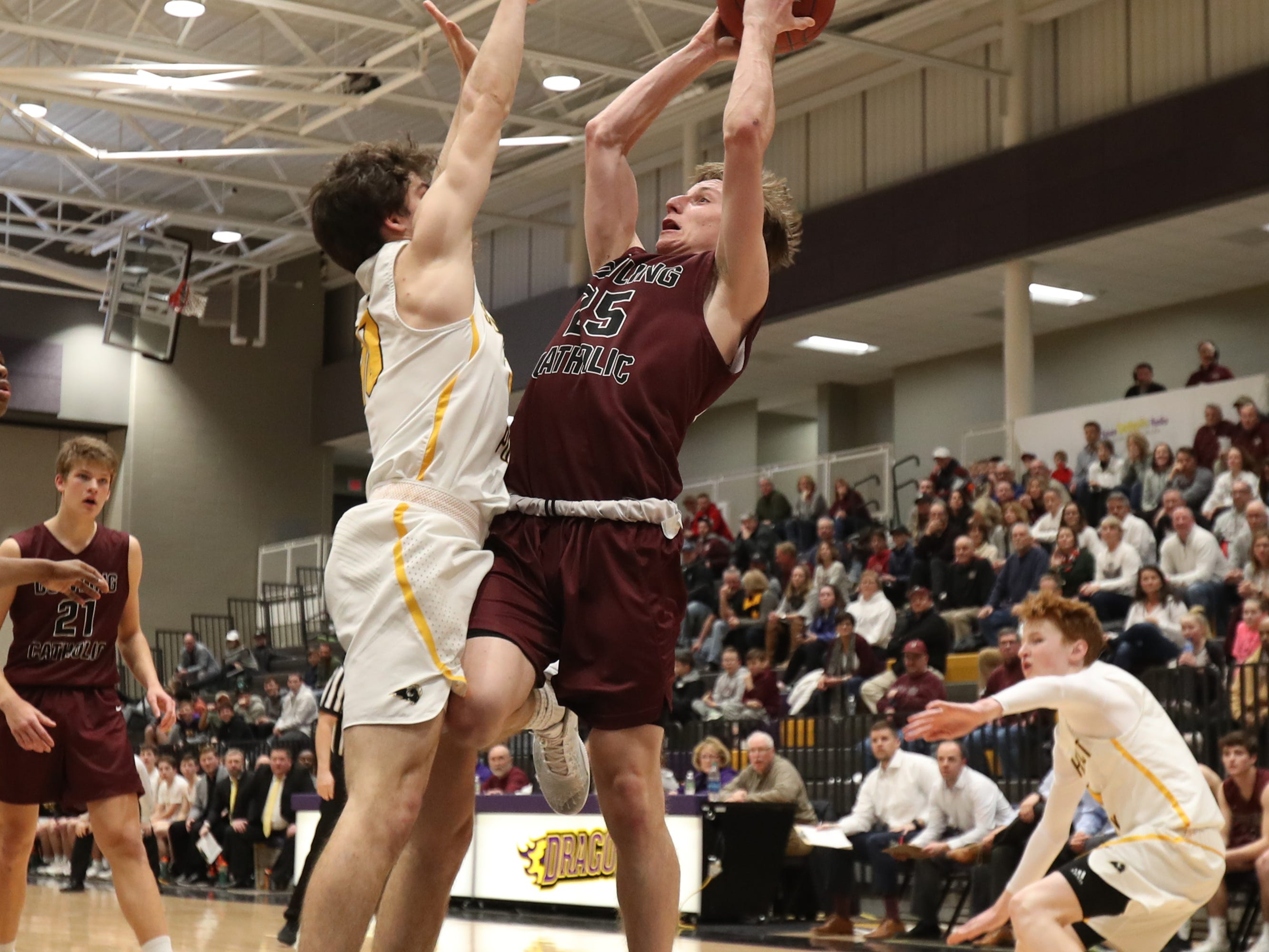 Dowling Catholic's Matt Stilwill (25) shoots over the top of Southeast Polk's Daniel Hackbarth (10) during their game at Johnston High School in Johnston, Iowa, on Tuesday, Feb. 26, 2019. Dowling won the game 44-40 to advance to state.