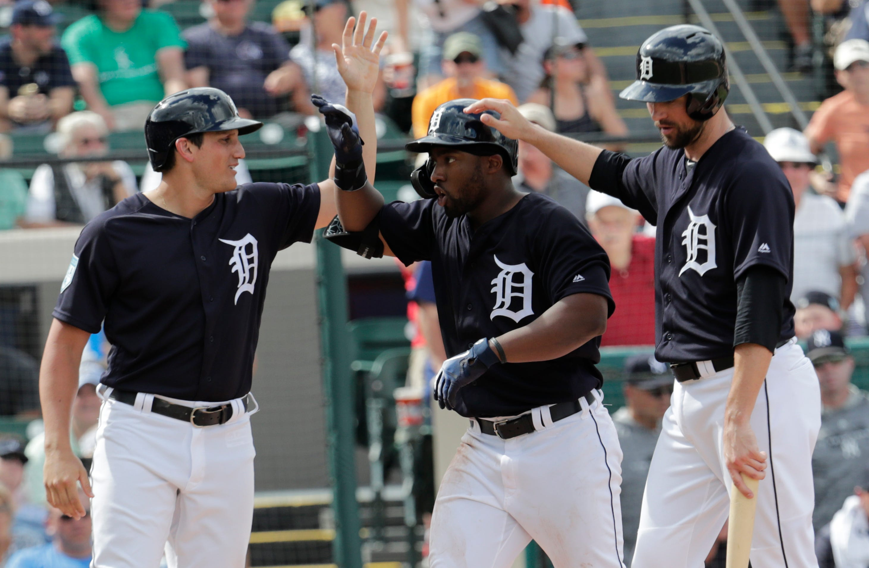 Tigers left fielder Christin Stewart, center, is congratulated by Jordy Mercer, left, and Mikie Mahtook after hitting a grand slam in the third inning of the spring training baseball game against the Yankees on Wednesday, Feb. 27, 2019, in Lakeland, Fla.