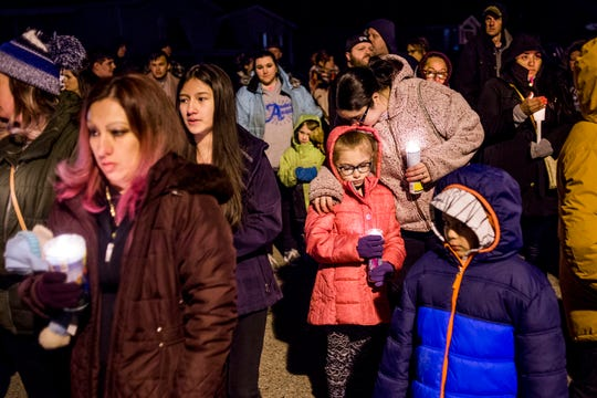 Imlay City resident Elizabeth Parrott leans down to kiss her 7-year-old daughter Aunnalee as they pay their respects during a vigil alongside more than 100 people that gather to commemorate the lives of three children who died in an early morning fire at a mobile home park Tuesday, Feb. 26, 2019, in Imlay City. Several additional family members were hospitalized and listed in critical condition.