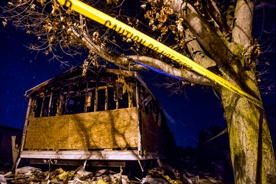 Police tape stretches taut across the lawn outside of the charred shell of a home where a family lost several children to an early morning fire at a mobile home park Tuesday, Feb. 26, 2019, in Imlay City. Other family members were critically injured due to the fire which is under investigation and hospitalized.