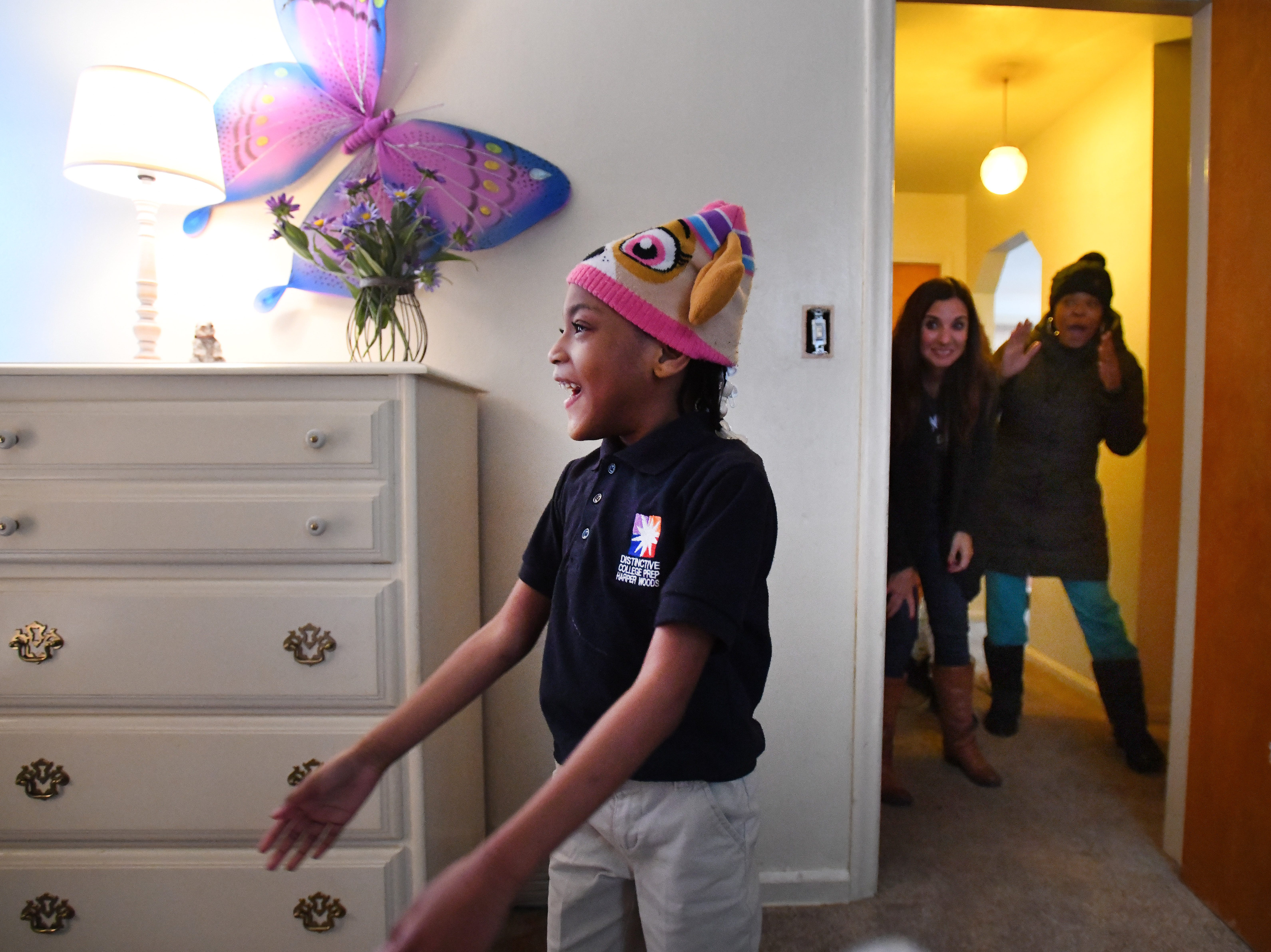 Seven-year-old Ja'Kayla Powers-McCoy reacts with delight as she enters her newly decorated room full of pink and purple, as Humble Design CEO and Co-founder Treger Strasberg and Ja'Kayla's mother Jamiliah Powers-McCoy watch from the hallway.