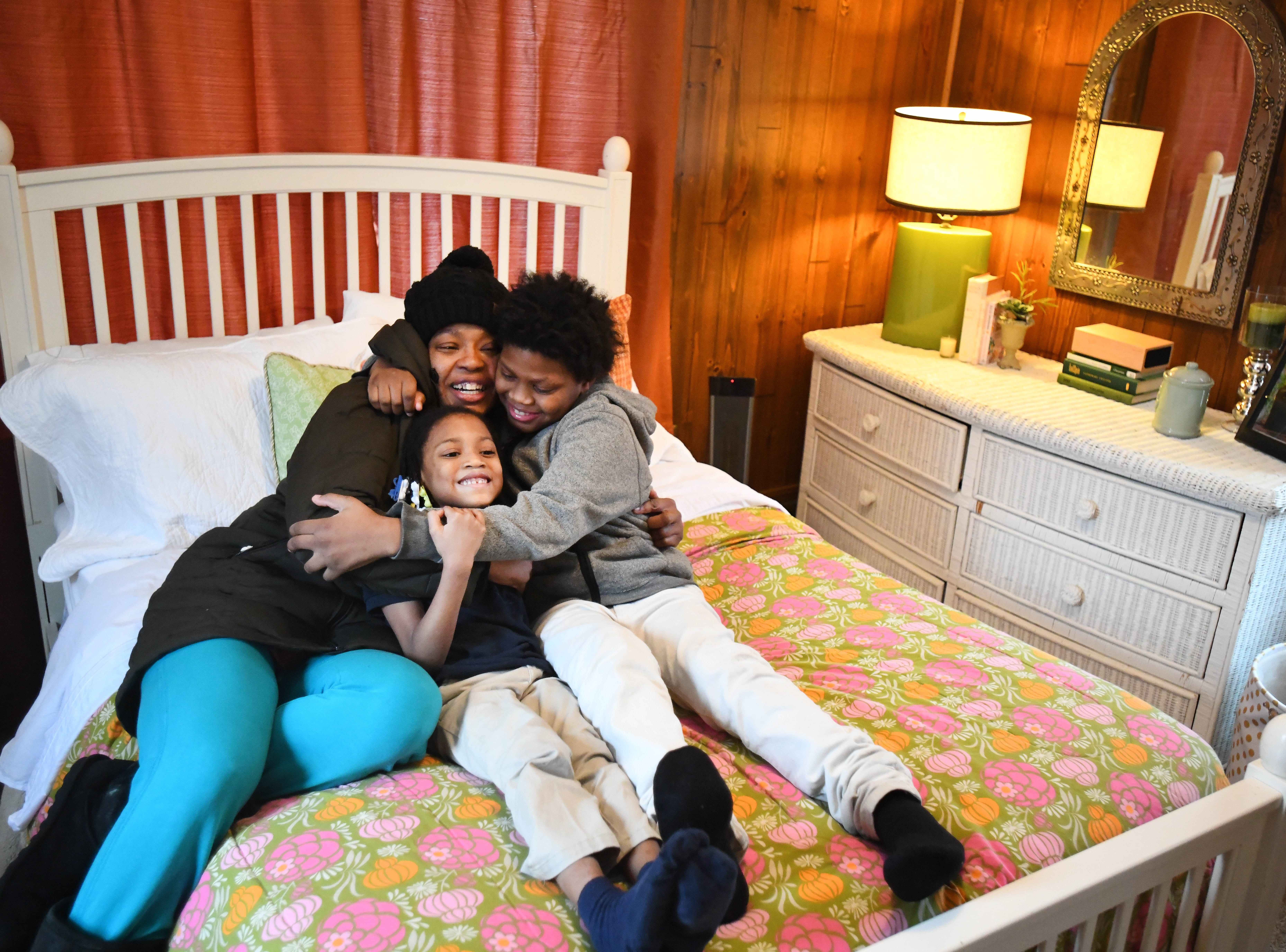 "Jamiliah Powers-McCoy hugs her daughter Ja'Kayla, 7, and son Jai'Vonte, 12, on the bed in her newly furnished bedroom. ""I won't have to sleep on the floor no more,"" she said. Humble Design, a nonprofit that furnishes homes for people coming out of homelessness unveiled their 1000th home in Detroit on Feb. 27, 2019."