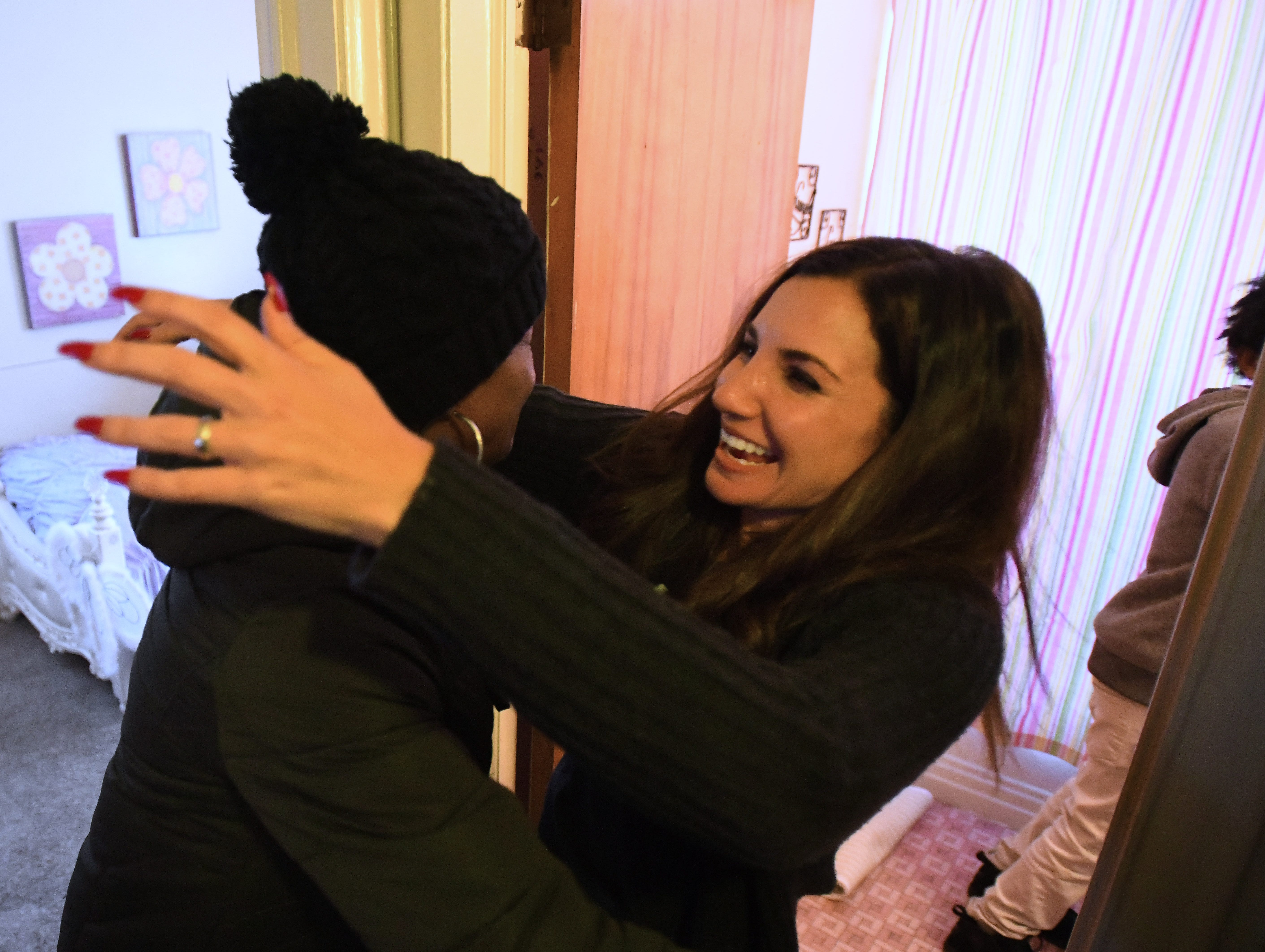 Jamiliah Powers-McCoy, left, and Humble Design CEO and co-founder Treger Strasberg hug during the reveal of her newly designed and furnished home.