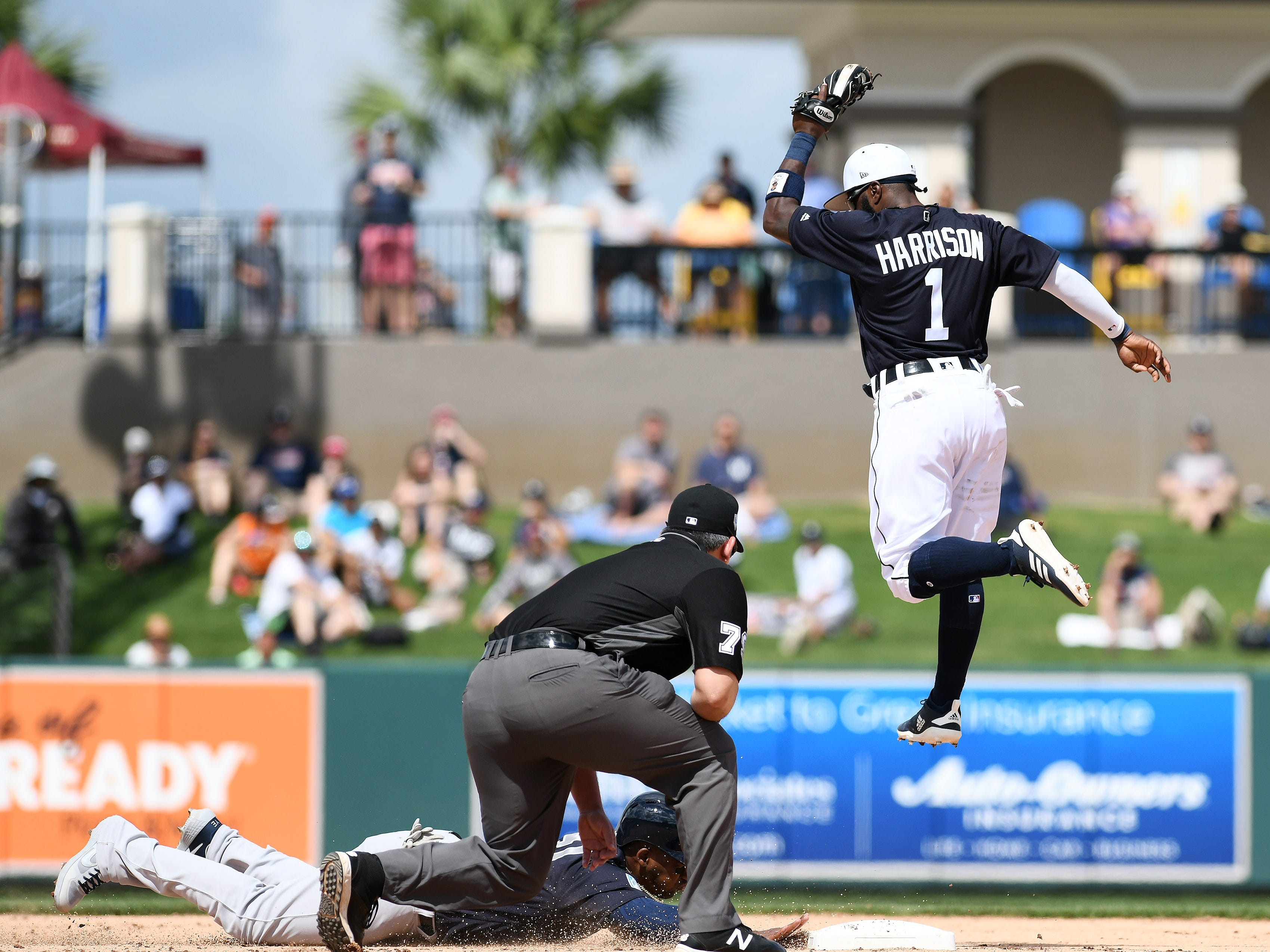 Tigers second baseman Josh Harrison goes airborne to catch a throw in the first inning.