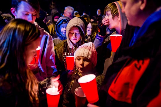 Makenzie Craven, 10, of Imlay City, bows her head Tuesday night alongside her family as she commemorates the lives of several children who died in a Tuesday morning fire at a mobile home park Imlay City.