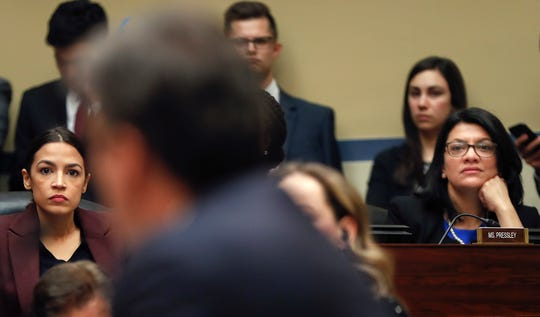 Committee members Rep. Alexandria Ocasio-Cortez, D-N.Y.,, left, and Rep. Rashida Tlaib, D-Mich., right, listen to Michael Cohen, center, President Donald Trump's former lawyer, testimony before the House Oversight and Reform Committee on Capitol Hill.