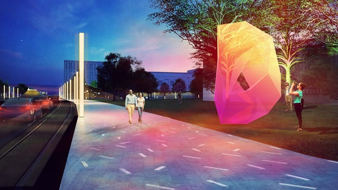 """Pedestrians pass one of the """"Gateways,"""" shaped like an abstract D, that TENxTEN employs to announce your arrival in the cultural district."""