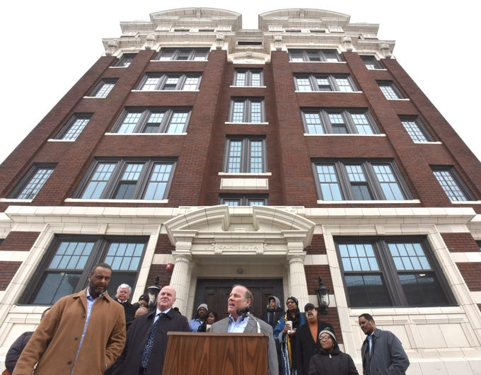 Detroit Mayor Mike Duggan, right, addresses attendees from the podium as CCIH President and CEO Ryan Lepper, left, and builder Joe Early, center, of Early Construction, listen during a press conference, Wednesday morning, February 27, 2019, in front of the renovated, historic Saint Rita Apartments building. Residents of the renovated building will be veterans, homeless individuals and Detroit residents with special needs.
