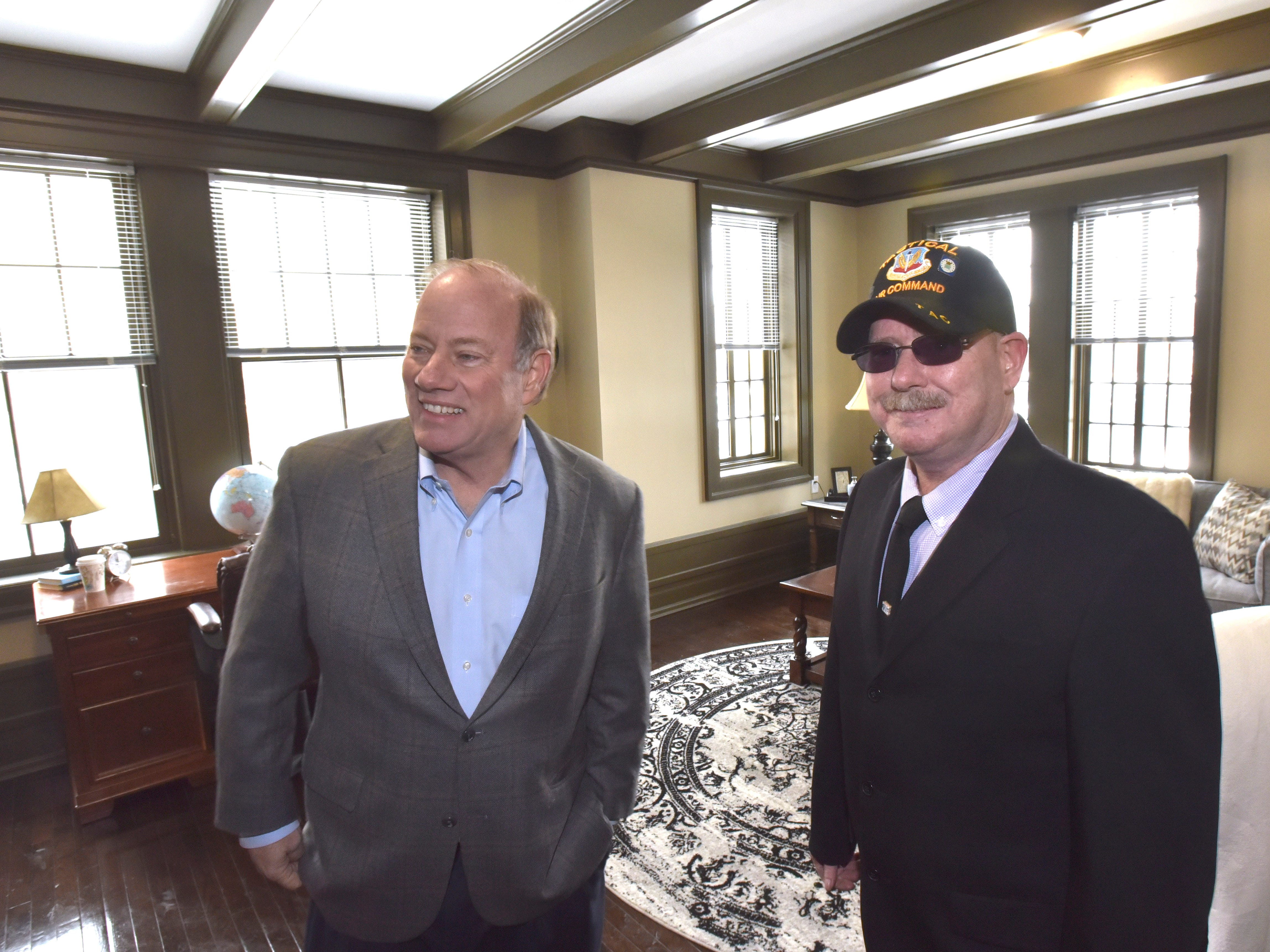 Detroit Mayor Mike Duggan, left, and resident Jonathon Fisher, right, stand in Fisher's future living room. He is a former U.S. Air Force Crew Chief with the Tactical Air Command.