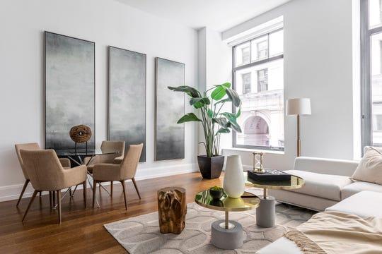 Indigo art panels help frame a dining seating area in an urban apartment. (Design Recipes/TNS)