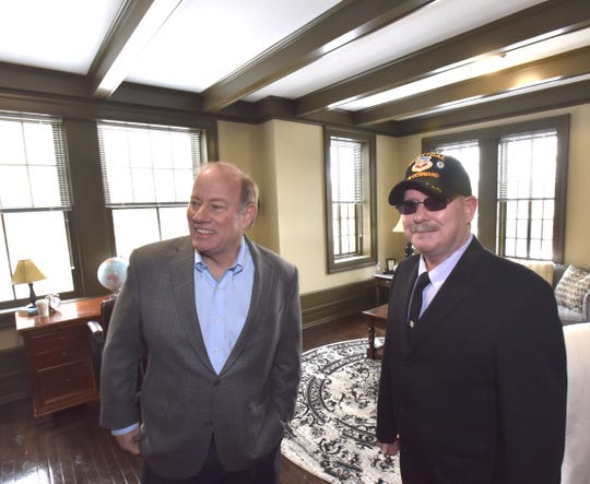 Detroit Mayor Mike Duggan, left, and resident Jonathon Fisher, right, stand in Fisher's future living room at the Saint Rita Apartments. He is a former U.S. Air Force Crew Chief with the Tactical Air Command.