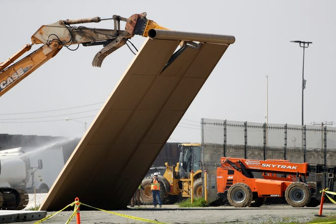 A border wall prototype falls during demolition at the border between Tijuana, Mexico, and San Diego, Wednesday, Feb. 27, 2019.