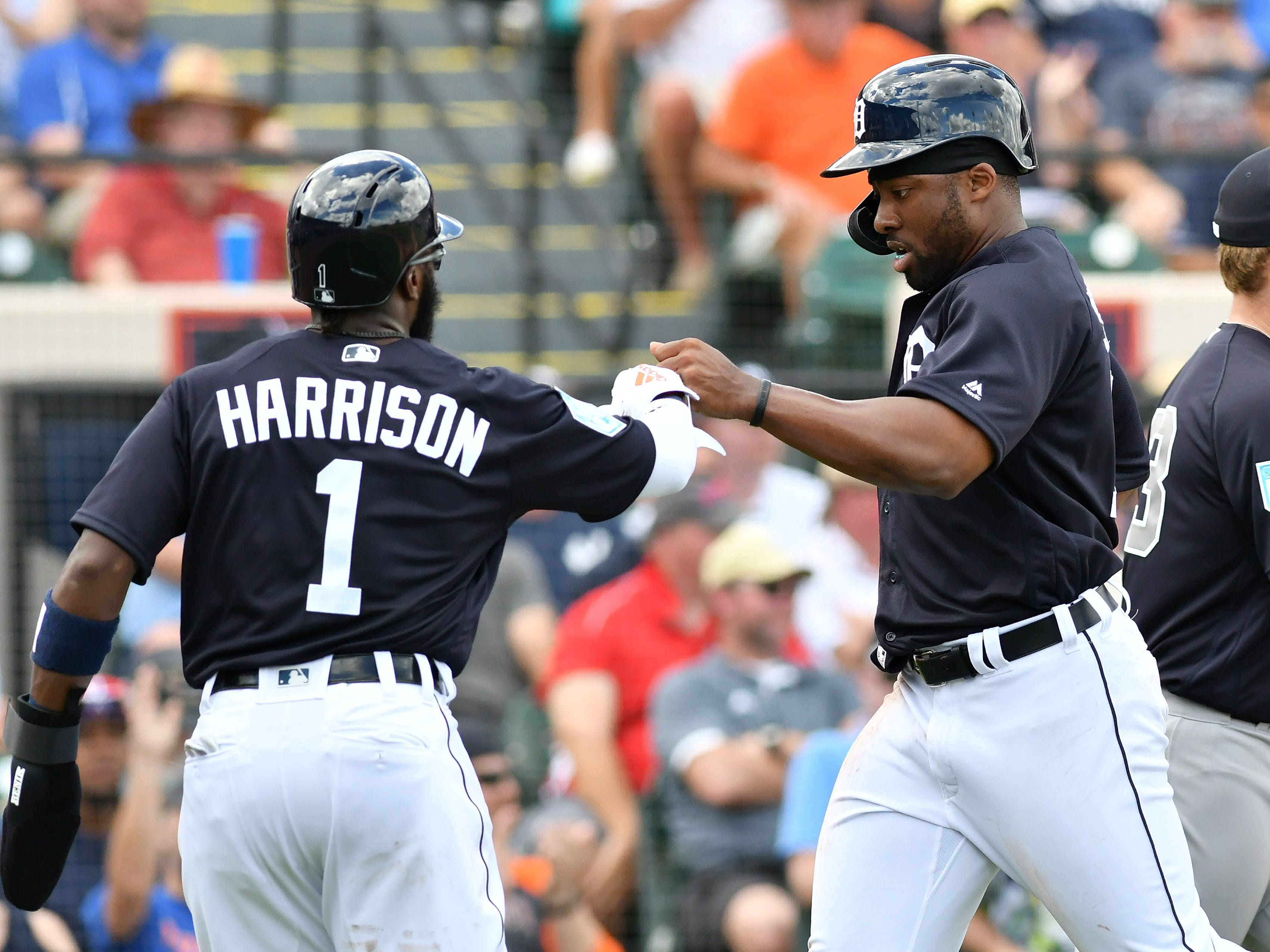 Tigers' Josh Harrison (1) and Christin Stewart after they score on a double by Nicholas Castellanos, not shown, in the first inning.