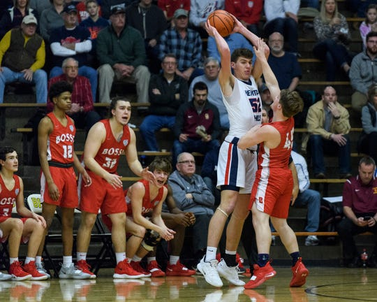 Bosse's Kolten Sanford (45) guards Heritage Hills' Blake Sisley (52) during the IHSAA Class 3A first-round sectional game at Boonville High School in Boonville, Ind., Tuesday, Feb. 26, 2019. The Bulldogs beat Heritage Hills, 66-62, to advance to Friday's 6 p.m. semifinal match-up against Memorial.