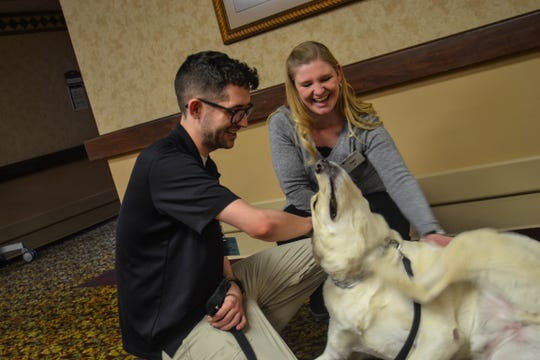 Amos gets a three-way scratch with Cody Russell, a certified resident care associate for Genoa Retirement Village, and Amy Gyuras, an RN with Hospice of Northwest Ohio. Amos had spent the morning visiting residents at Genoa Retirement Village.