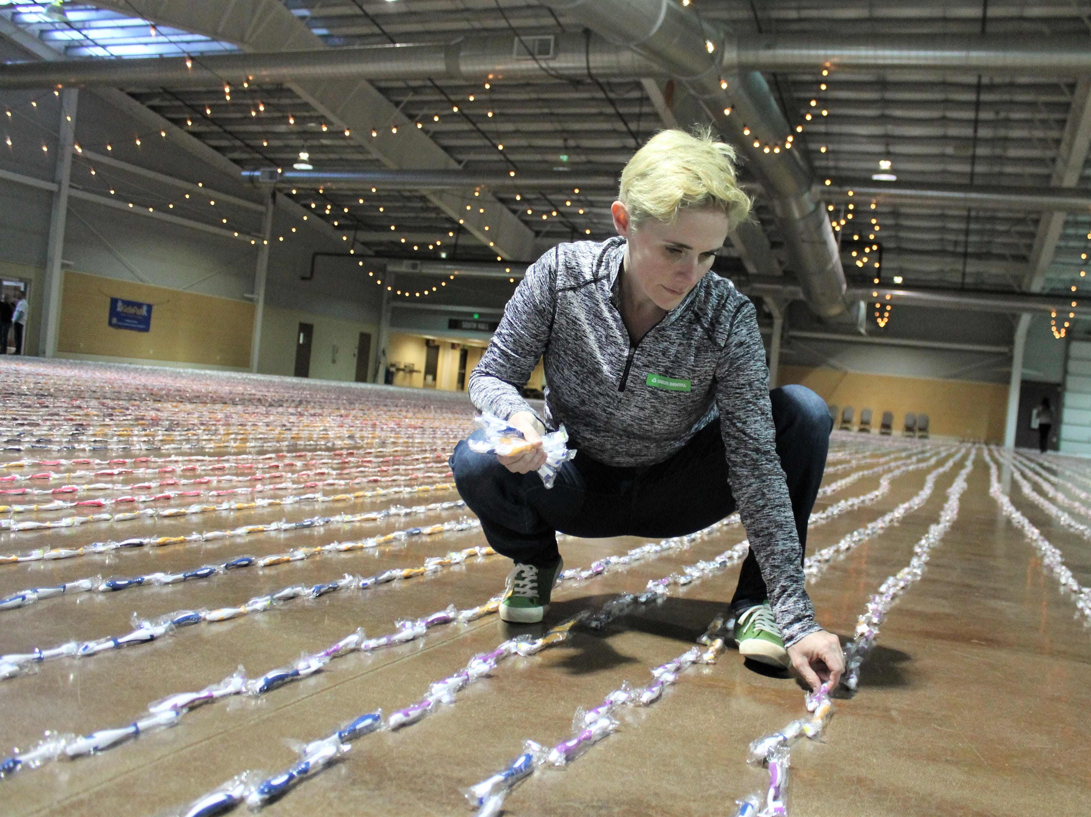 Andrea Miller works to straighten out a line of toothbrushes Feb. 26, 2019 at The Ranch Event Complex in Loveland. She, along with about 60 other volunteers, came together to break the Guinness World Record for most toothbrushes organized in a continuous line. The organizer, Change Gangs: Virtual Giving Circles will donate about 55,000 toothbrushes to kids in need across Colorado.