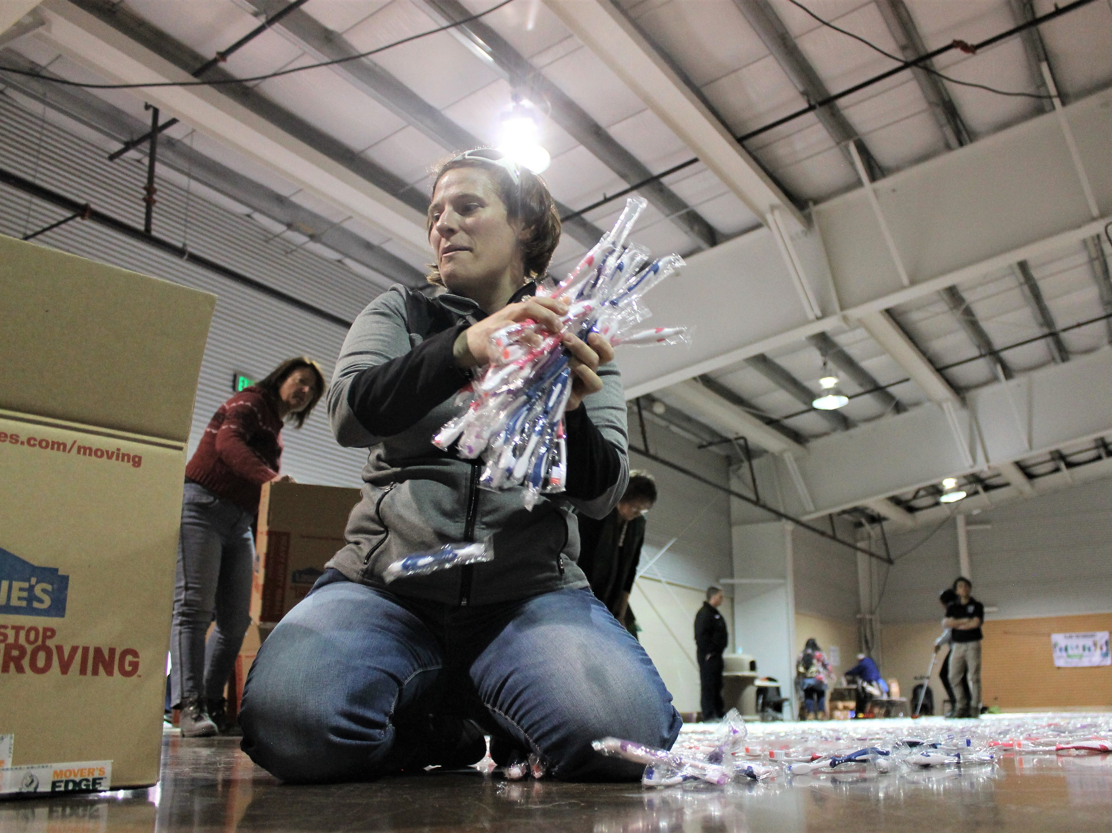Katie Houghtlin puts piles of new toothbrushes into a box Feb. 26, 2019 at The Ranch Event Complex in Loveland. About 60 volunteers came together to break the Guinness World Record for most toothbrushes organized into a continuous line. At 41,769 toothbrushes, organizer Change Gangs: Virtual Giving Circles made history. The group will donate about 55,000 toothbrushes to kids in need across Colorado.