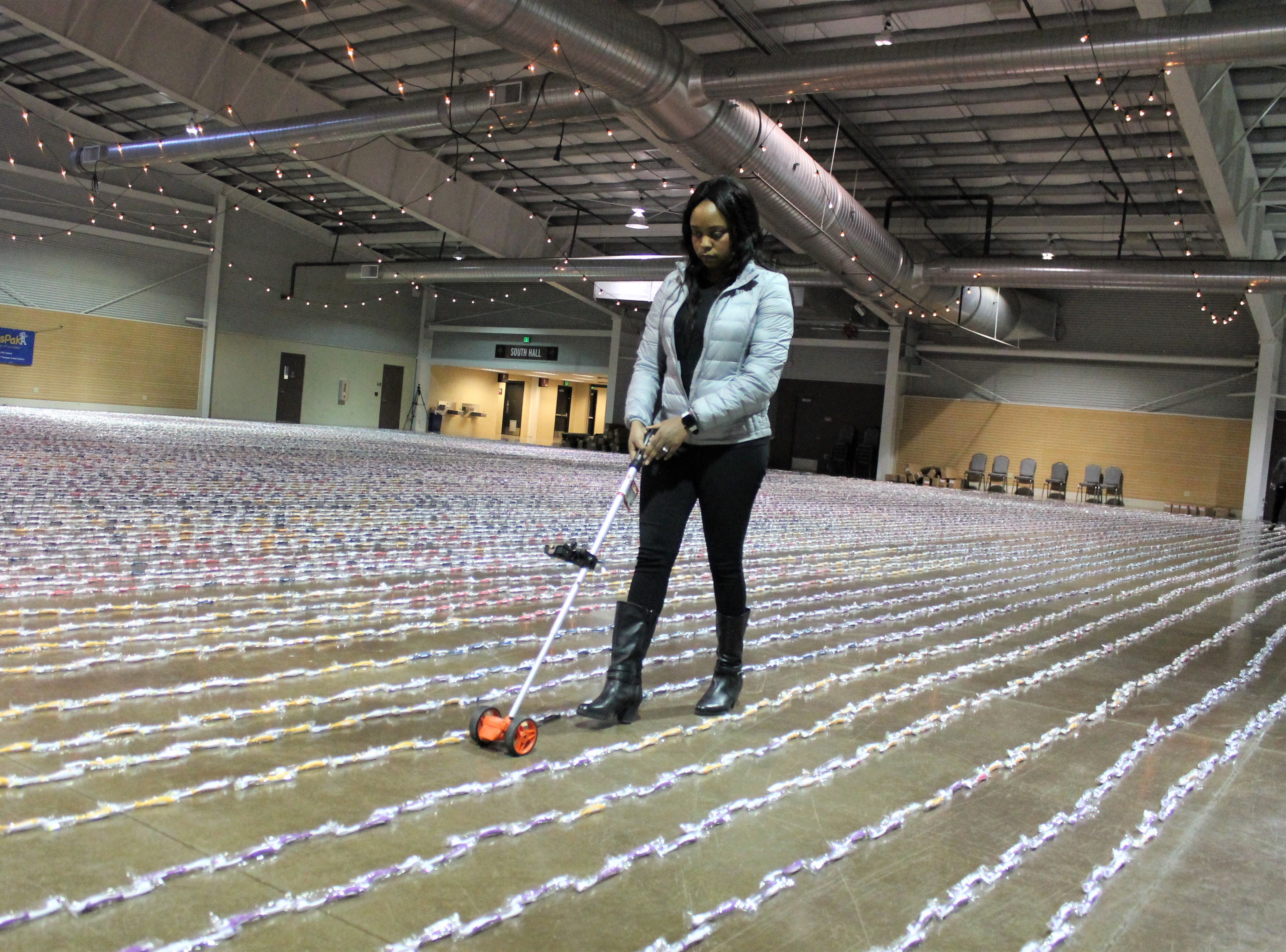 Stacey  Smith, a volunteer with Change Gangs: Virtual Giving Circles, measures and records rows of toothbrushes at The Ranch Event Complex in Loveland Feb. 26, 2019. Organizers lined up more than 40,000 toothbrushes to break the Guinness World Record. The toothbrushes will be donated to kids in need across Colorado.