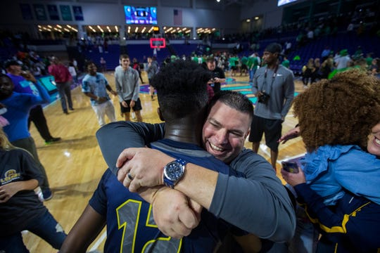 Lehigh Senior High basketball coach Greg Coleman Jr. embraces Quinton Desamours after defeating Fort Myers 65-60 in overtime in a Class 7A regional semifinal at Suncoast Credit Union Arena on Tuesday, February 26, 2019.
