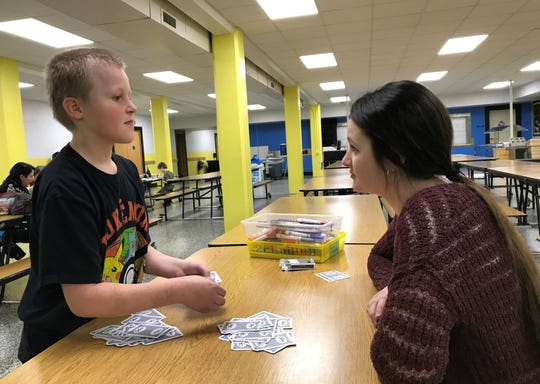 Algoma Elementary School fifth-grade student Dylan Spence Anderson, left, deals cards for a game of War with Algoma High School senior Abigail Robinson during a Wolf Den gathering at the elementary school. Robinson launched the Wolf/Pup and Wof Den mentoring programs matching high school students with selected elementary school students such as Anderson.