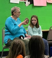 "Jane Button, called ""Grandma Button"" by Pups in the Wolf Den program, talks about the piece of amethyst she brought for a pre-dinner show-and-tell at the Feb. 19 Wolf Den at Algoma Elementary School. Watching on at Button's left is student Cierra Bliss."