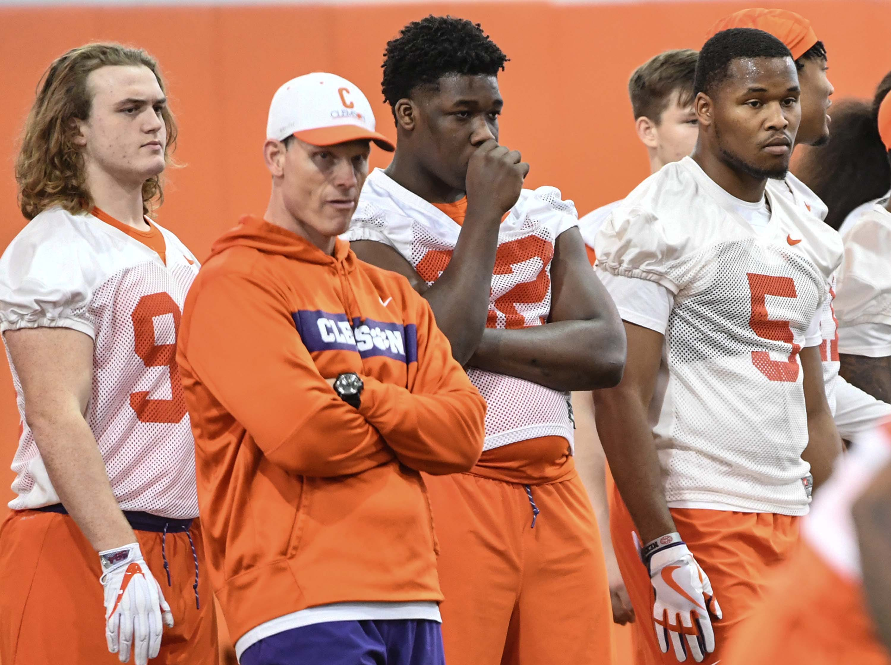 Clemson defensive coordinator Brent Venables, middle, stands with Logan Cash (98), left, and Clemson defensive lineman Etinosa Reuben (32), and Clemson linebacker Shaq Smith (5) during the first practice at the Clemson Indoor Practice Facility in Clemson Wednesday, February 27, 2019.