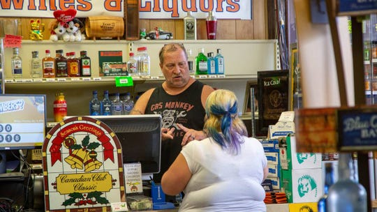 Robert Pereksta, owner of Gator's Liquors in Surfside Beach, talks with a customer at the store on Thursday. Pereksta says he plans to reopen again Saturday.