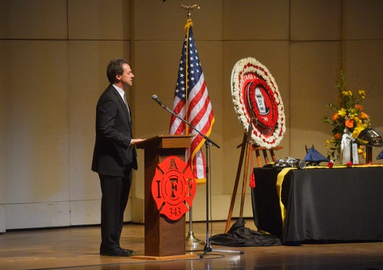 Governor Steve Bullock honors Great Falls firefighter Jason Baker during Tuesday's memorial service in the Mansfield Theater.