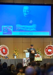 A member of the Montana State Fireman's Association Honor Guard carries the ashes of Jason Baker from the Mansfield Auditorium on Tuesday.  Baker passed away on February 20th at the age of 45 after a two-year battle with lung cancer.