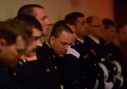 """Billings firefighter Ryan Smith wipes away tears during the """"End of Watch Call"""" for Great Falls firefighter Jason Baker during a memorial service, Tuesday in the Mansfield Auditorium.  Baker passed away on February 20th after a two-year battle with lung cancer."""