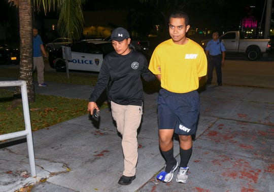 Restrained in handcuffs, Vianney Nennis Hosei, 18, is escorted by Guam Police Department Criminal Investigation Division detectives into the agency's Hagåtña Precinct, just after midnight on Thursday morning, Feb. 28, 2019.
