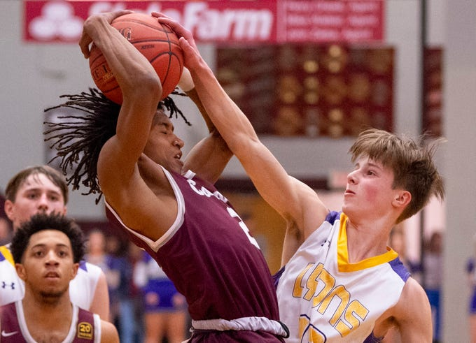 Henderson County's Zac Green (2) pulls down a rebound against Lyon County's Travis Perry (11) during the Boys Second Region Tournament at Madisonville-North Hopkins High School Tuesday night.