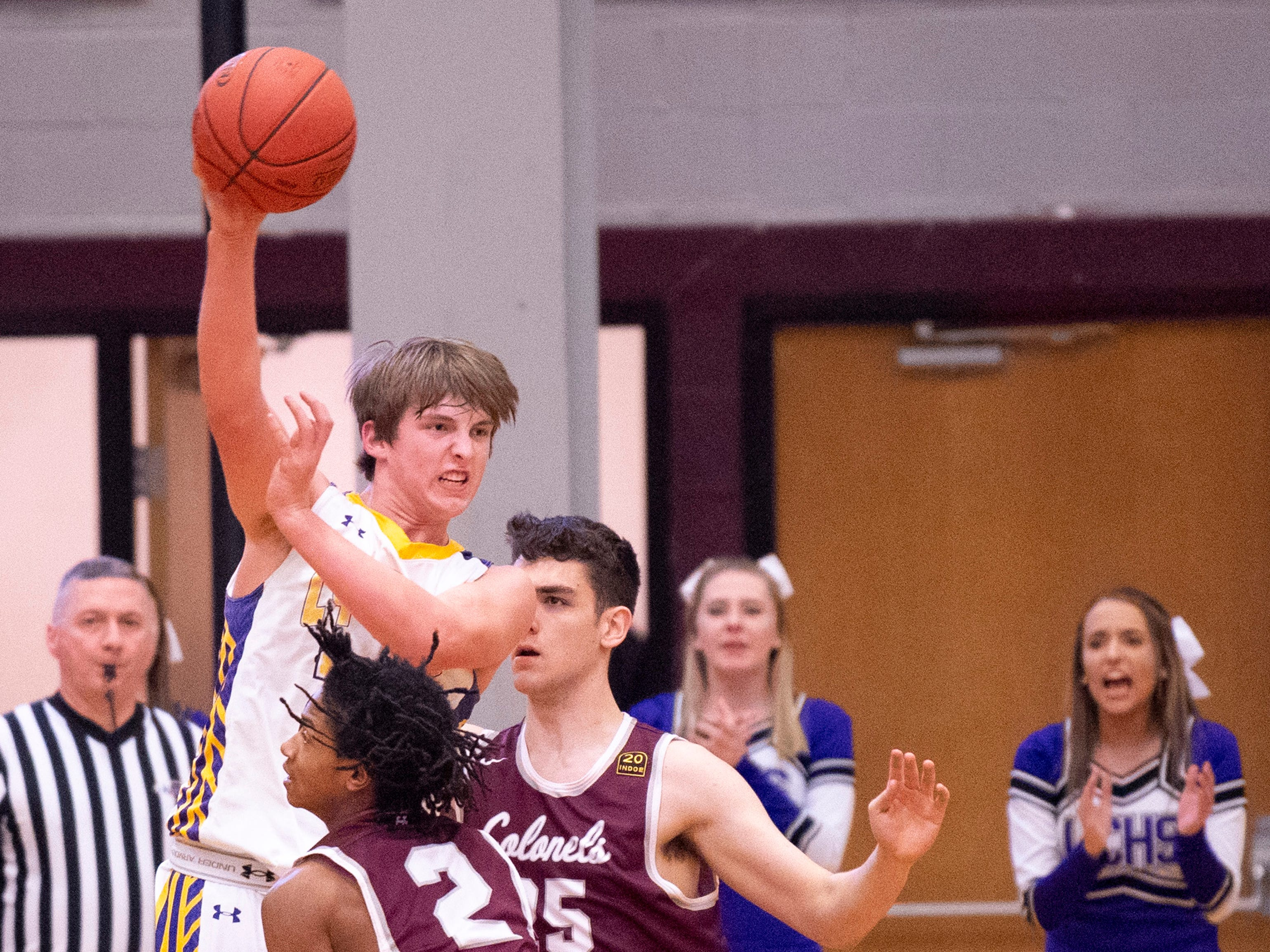 Lyon County's Jackson (23) passes over the Henderson County defense of Zac Green (2) and Alec Agnew (25) during the Boys Second Region Tournament at Madisonville-North Hopkins High School Tuesday night.