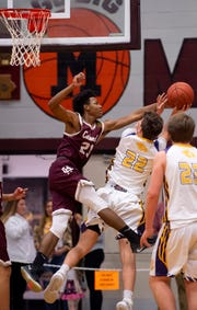 Henderson County's Myekel Sanners (23) blocks Lyon County's Gabe Board (22) during the Boys Second Region Tournament at Madisonville-North Hopkins High School Tuesday night.