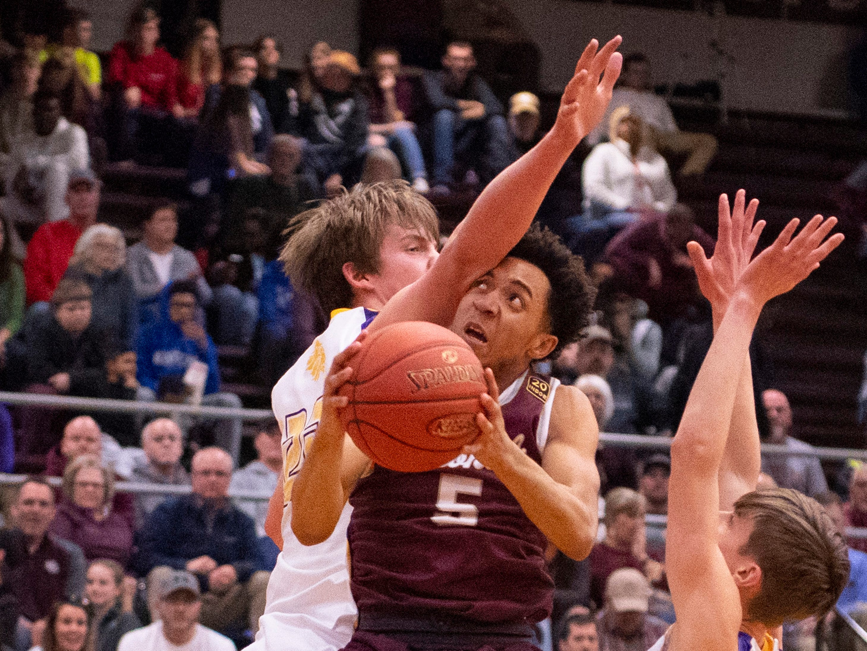 Henderson County's Edmund Brooks (5) is hit by a Lyon County player, but still made the shot during the Boys Second Region Tournament at Madisonville-North Hopkins High School Tuesday night.