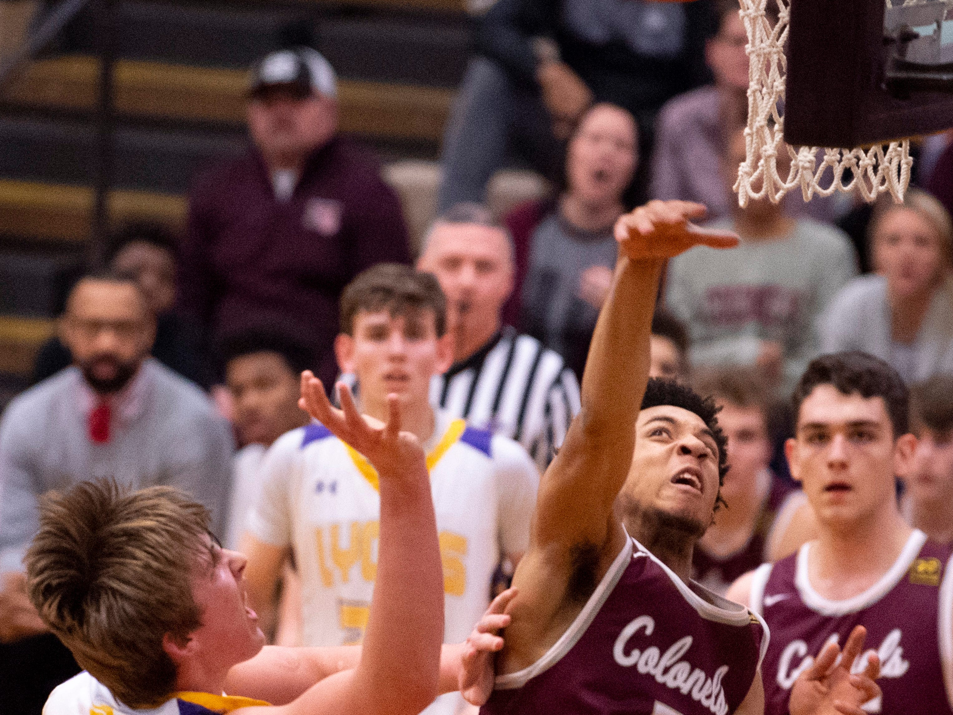 Henderson County's Edmund Brooks (5) and Lyon County's Jackson Shoulders (23) go up for a rebound during the Boys Second Region Tournament at Madisonville-North Hopkins High School Tuesday night.