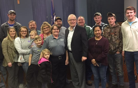 Mayor Steve Austin poses with Debra Grant, her family and friends Tuesday evening after awarding her a 35-year city service pin. She is a school crossing guard that works for the Henderson Police Department.